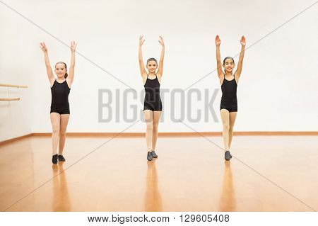 Full length portrait of three little girls preparing themselves to do some flips in dance class and smiling