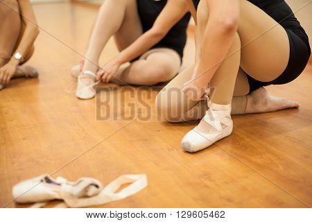 Closeup of a group of young women getting ready for dance practice and putting their shoes on