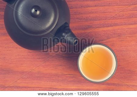 Clay glazed bowl with brewed tea and clay teapot on red wooden table top view with space for text, vintage filtered