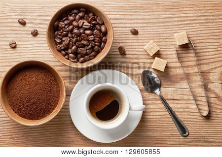 Coffee beans, ground coffee and cup of brewed coffee on rustic wooden table with spoon, sugar tongs, cane sugar cubes and coffee beans, view from above