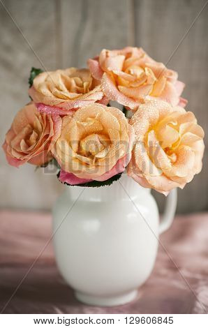 bouquet of pink roses with a yellow tinge in white jug