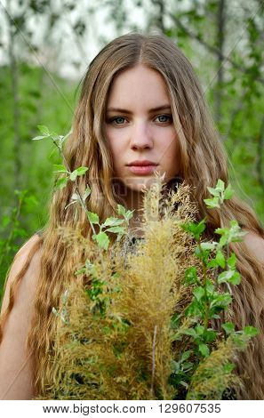 The portrait of spring girl in green trees, flowers, garden, park. Long-haired, light-haired, blonde girl, woman with bouquet of green flowers in hands. Springtime. Beautiful, awesome girl.