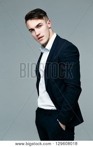 Handsome stylish man in elegant black suit and black pants on gray background