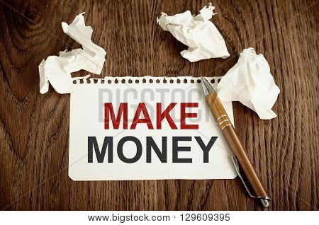 Make Money. Written on white paper on wooden background