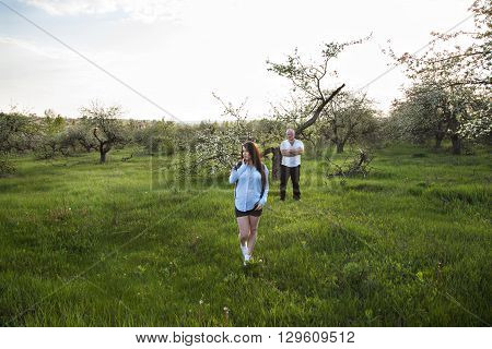 young beautiful couple waiting baby stands on a meadow at a distance from each other. the man behind the woman looks at her with arms folded