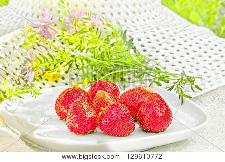 Red ripe strawberries on a white plate in the summer garden on a background of white hat and wildflowers backlit. Selective focus