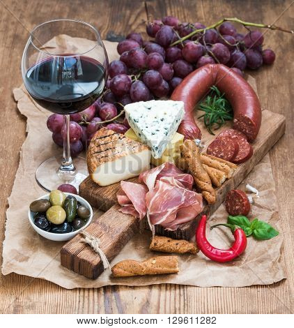 Glass of red wine, cheese and meat board, grapes, fig, strawberries, honey and bread sticks  on rustic wooden table, white background, selective focus