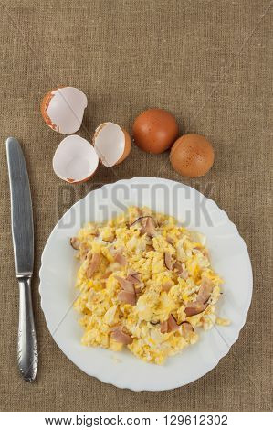 Fried scrambled eggs on a plate. Hearty meals for athletes. Diet Food. Traditional breakfast on the table. Domestic eggs.