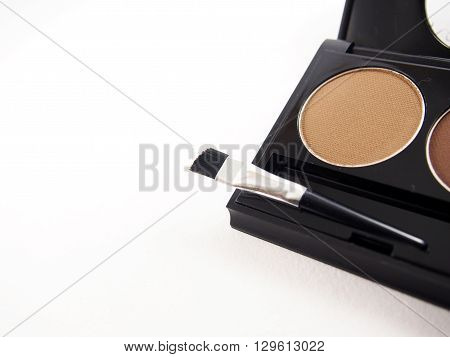 Eyebrow makeup, brown powder with brush on white background