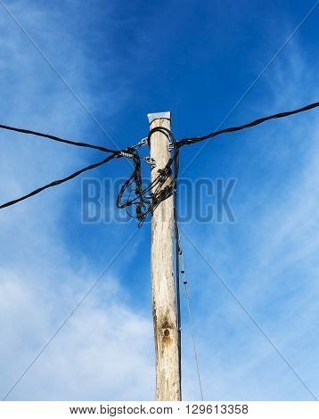 Wooden electric pole with some cable lines.