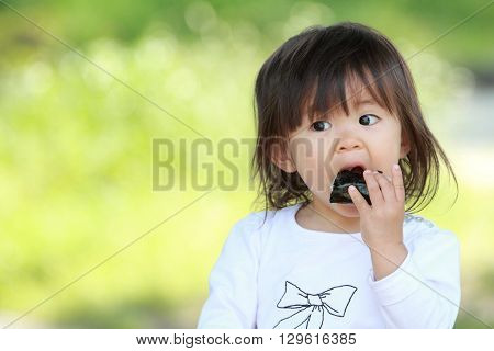 Japanese girl eating rice ball (1 year old)