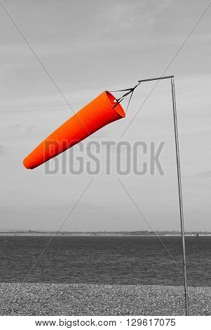 Orange windsock by the sea blowing in the wind in a black and white background.