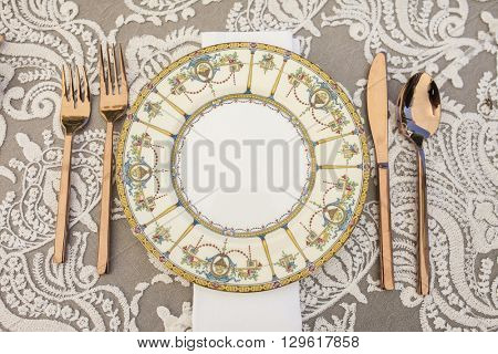 Vintage table setting with antique plate and silverware