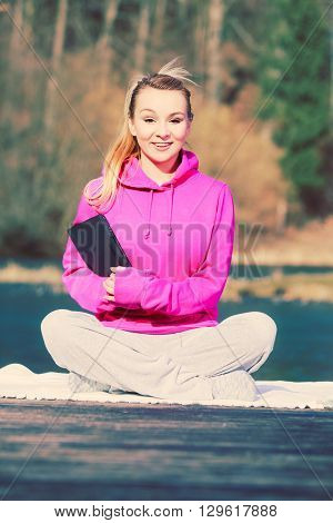 Young girl sitting in park learning yoga from tablet. Taking care about healthy lifestyle and slim figure. Sport with technology.