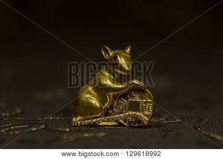 Mouse keeps coin Feng Shui for wealth on dark background