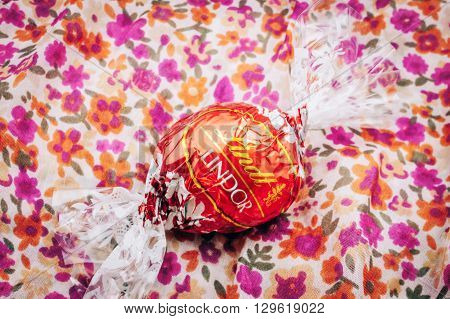 KILCHBERG SWITZERLAND - MARCH 20 2014: Beautiful Lindt Lindor chocolate truffle on a red luxury silk background. Lindt is one one of the lastgest luxury chocolate and confectionery company worldwide with more than 30 factories worldwide
