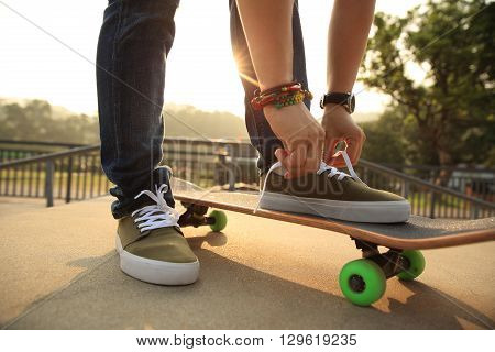 young skateboarder tying shoelace at skatepark ramp