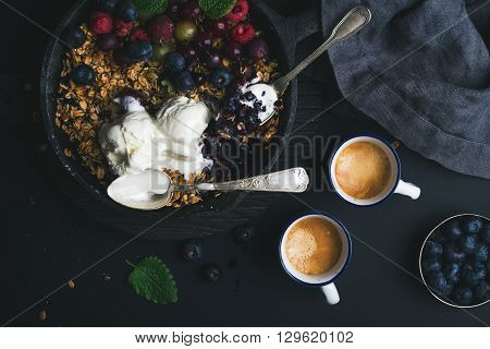Healthy breakfast. Oat granola crumble with fresh berries, seeds and ice-cream in iron skillet pan on dark wooden board and cups of coffee over black backdrop, top view