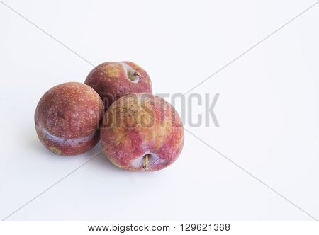 Ripe plums and cherry-plum on a white table