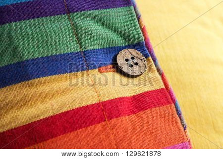 The texture and colors of a striped cushion cover, in closeup.