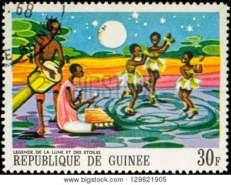 MOSCOW RUSSIA - MAY 12 2016: A stamp printed in Guinea shows three dancing black girls - scene from Legend of the moon and the stars series