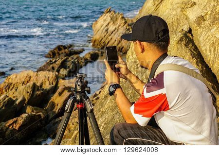 Labuan,Malaysia-April 2,2016:Man taking photo with smart phone camera enjoying natural scenery at Labuan beach.Smart phone camera are getting better all the time at taking photos with big megapixel.