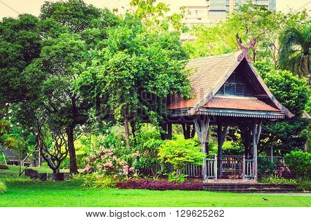 Big wooden asian country style pavilion in the beautiful garden with flowers and trees. Selective focus toned