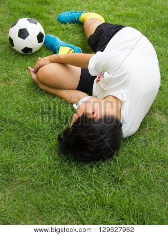 Football player lying injured on the pitch.