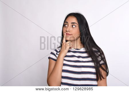 Young beautiful woman thoughtful in studio. Isolated white background.