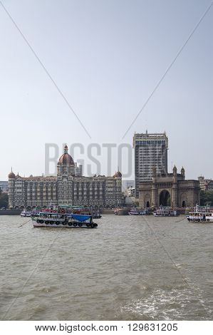 MUMBAI, INDIA - OCTOBER 11, 2015: Boats in front of the Taj Mahal Palace Hotel. This 5 star hotel is considered the flagship property of the group and contains 560 rooms and 44 suites. There are around 1500 staff including 35 butlers.
