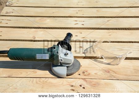 Angle grinder with abrasive disc and protective glasses on planks after work.