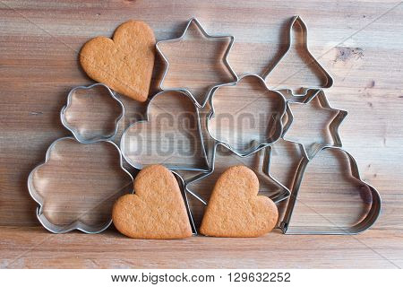 Christmas cookie cutters and gingerbread heart shaped cookies on wooden background
