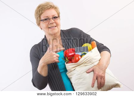Elderly senior woman with fruits and vegetables in shopping bag showing credit card paying for shopping and healthy nutrition in old age