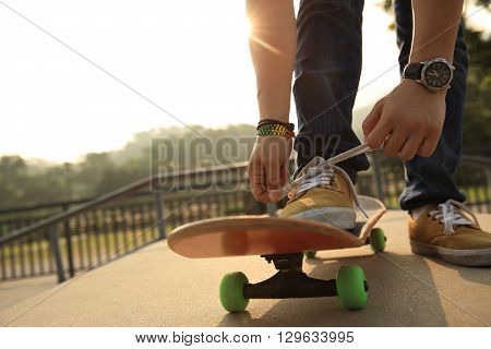 young skateboarder tying shoelace at sunrise skatepark