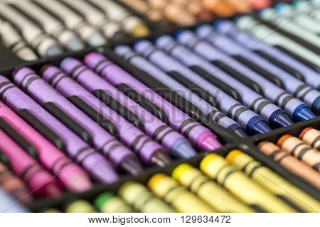 Set of multicolored professional artistic pastel crayons in open  box on table. Selective focus.