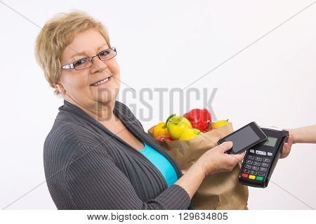 Elderly senior woman holding shopping bag and using payment terminal with mobile phone with NFC technology cashless paying for shopping healthy nutrition