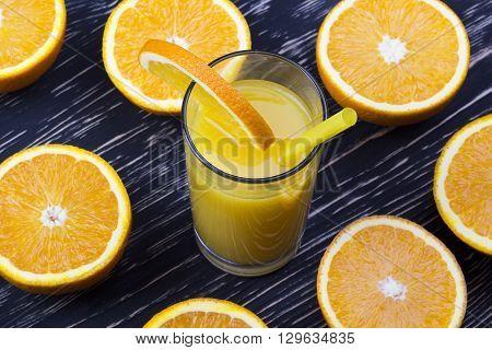 Orange juice in glass,  fresh fruits on black wooden background