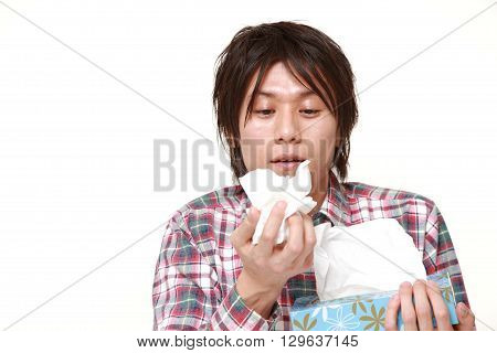 portrait of young man with an allergy sneezing into tissue on white background