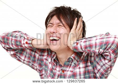 Young Japanese man suffers from noise on white background