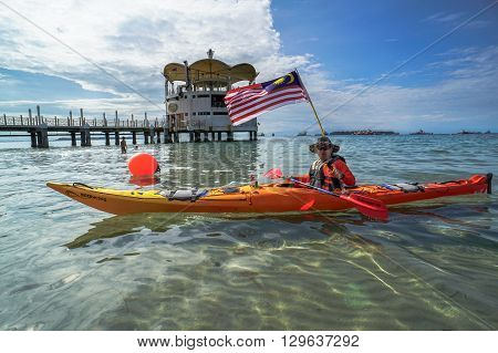 Labuan Malaysia - April 30, 2016:The adventurer smiling and enjoying sea kayak activity with Malaysia flag at Labuan International Sea Sports Complex at Labuan,Malaysia.