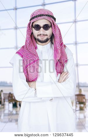 Portrait of Arabian person wearing headscarf while standing in the airport