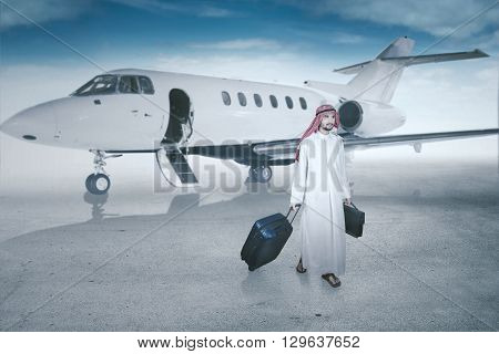 Successful Arabic businessman walking in the airport while carrying luggage with an aircraft on the back