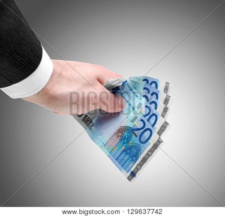 Businessman's hand holding a stack of twenty euro notes isolated on graduate background.