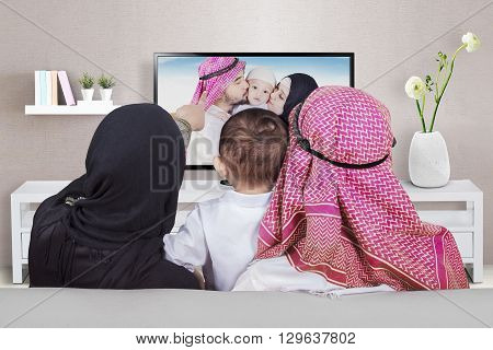 Arabian family sitting on the sofa while looking at their photo on the television shot at home