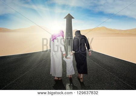 Back view of two Arabic parents and their son walking on the road with upward arrow