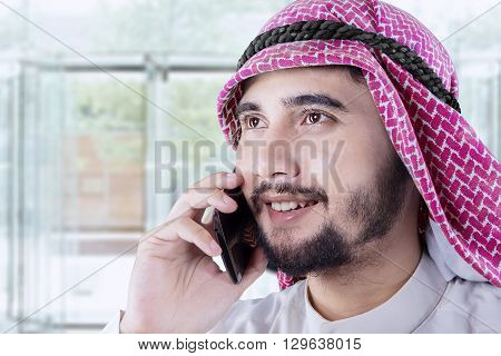 Photo of Arabian businessman talking on the mobile phone in the office lobby