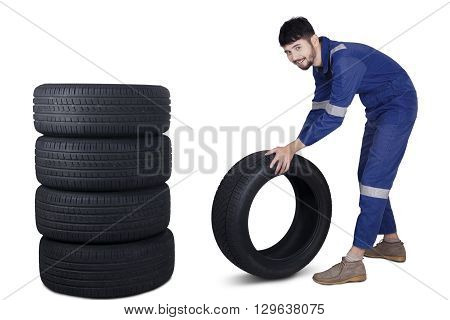 Portrait of Arabic mechanic smiling at the camera while pushing a tire with a pile of tires in the studio