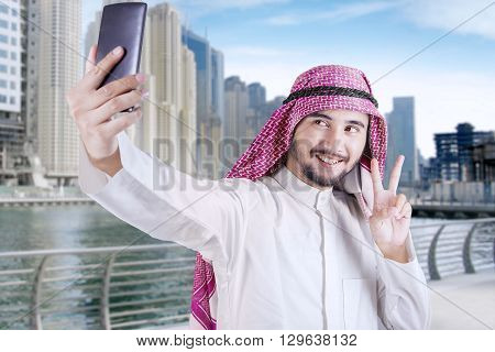 Happy Arabian person using a mobile phone to take selfie picture in the city