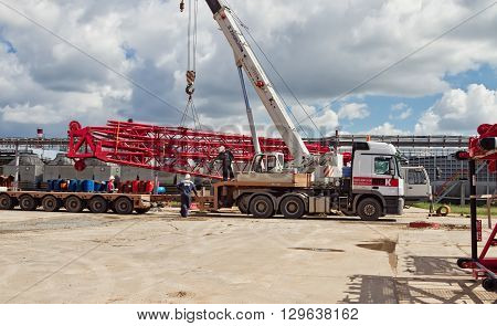 VOLGOGRAD - APRIL 28: Unloading sections of the boom of a large crawler crane using a crane on site of a petrochemical plant . April 28 2016 in Volgograd Russia.