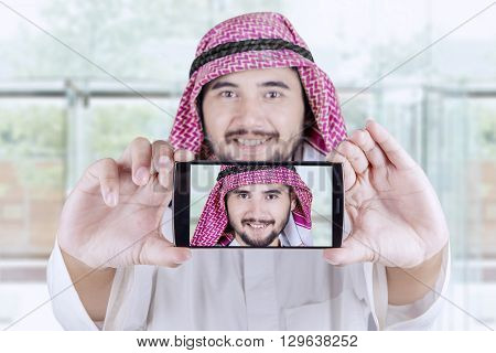 Portrait of Arabian businessman taking selfie photo with a smartphone in the office lobby